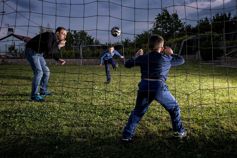 servizio fotografico DaddyCool | Foto di un papà e due figli che giocano a calcio